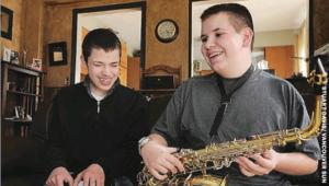 Alex Jurgensen and Matthew Alvernaz stand, facing the camera. Matthew is holding his Saxophone with Alex in the background.
