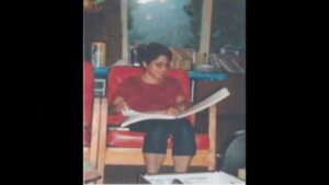A girl sitting in a chair, reading a Braille book.